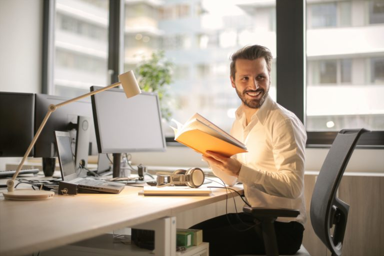 man holding a book happily working